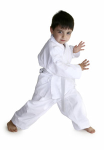 Four year old boy showing off his karate moves. Clipping path included.